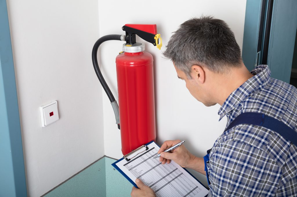 technician checking fire extinguisher